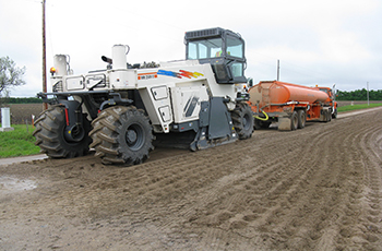 Image of maintenance vehicle applying base one with a reclaimer